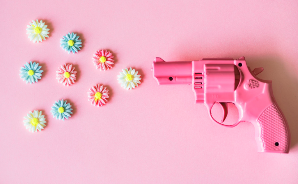 pink toy gun on pink background seemingly firing 9 little pretty flowers.